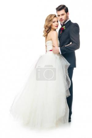 Photo for Side view of wedding couple hugging each other and looking at camera isolated on white - Royalty Free Image