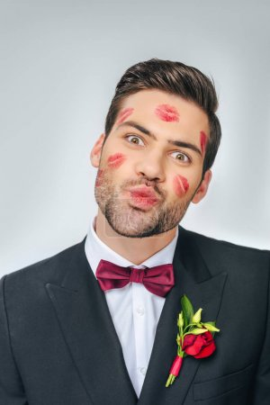 portrait of handsome groom in suit with red lipstick on face isolated on grey
