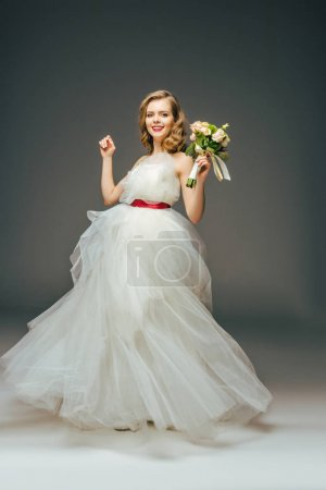 smiling bride in beautiful wedding dress with flowers in hand
