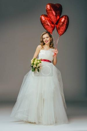 smiling bride in wedding dress with heart shaped balloons and bouquet of flowers