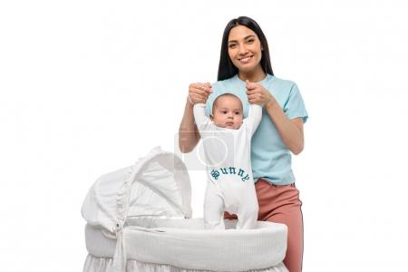 portrait of young woman and infant baby in crib isolated on white