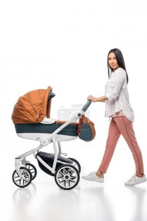 side view of young woman with infant baby in baby carriage isolated on white