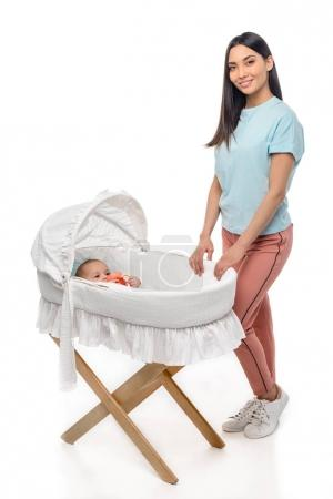 smiling woman standing near crib with infant baby isolated on white