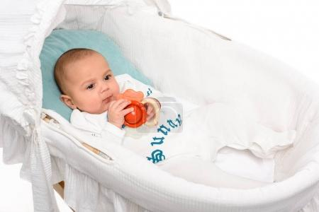 cute little baby with toy lying in crib isolated on white