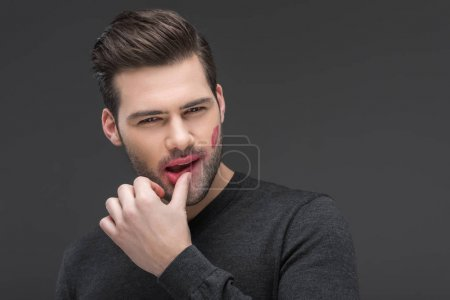 Photo for Handsome sexy man with kiss print on cheek, isolated on grey - Royalty Free Image