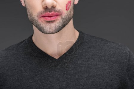cropped view of bearded man with kiss print on cheek, isolated on grey