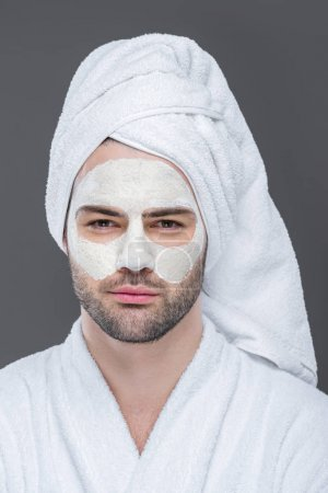 bearded man in towel with clay mask on face, isolated on grey, skin care concept