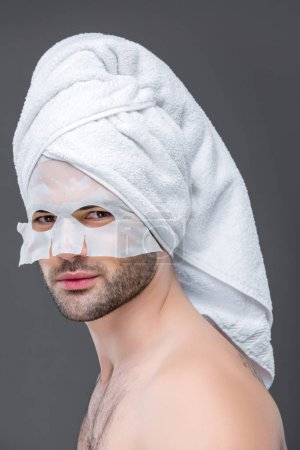 handsome man with towel and collagen mask, isolated on grey, skin care concept