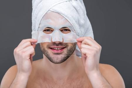 cheerful bearded man with towel and collagen mask, isolated on grey