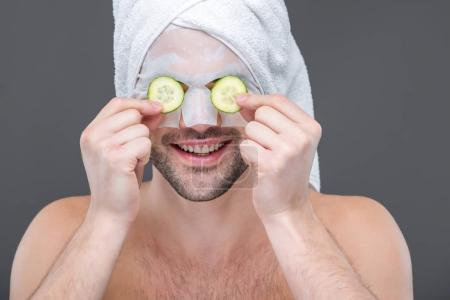 smiling bearded man with collagen mask and cucumber slices on eyes, isolated on grey