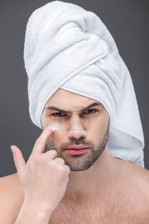 man in towel applying cosmetic cream on face, isolated on grey, skin care concept