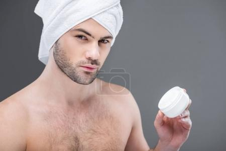 bearded man in towel holding face cream, isolated on grey