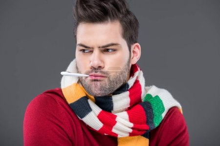 ill man with temperature in warm scarf, isolated on grey