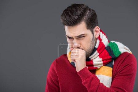 Photo pour Malade tousse dans une écharpe chaude, isolé sur gris - image libre de droit