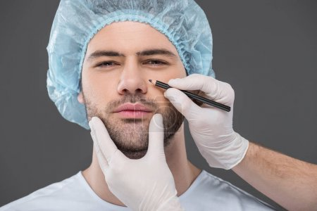 doctor drawing lines for facelifting on handsome man, isolated on grey