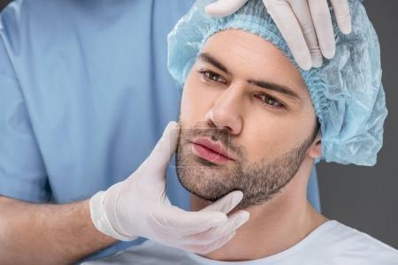 Photo pour Bel homme barbu en bonnet médical prêt à se relever, isolé sur gris - image libre de droit