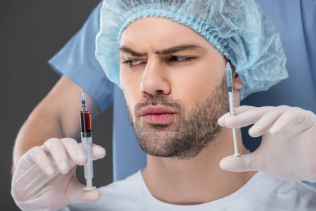 handsome man in medical cap choosing beauty injections, isolated on grey