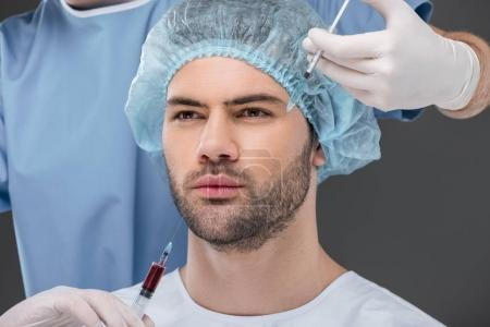 bearded handsome man in medical cap making beauty injections, isolated on grey