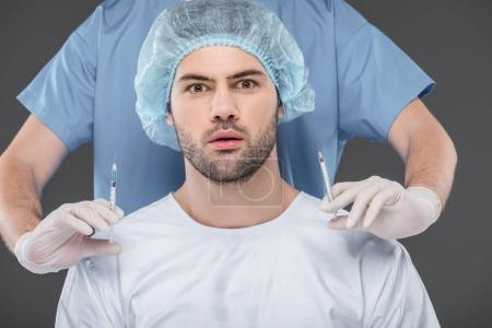 shocked handsome man in medical cap making beauty injections, isolated on grey