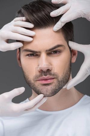 Foto de Barbudo hombre y médicos las manos, aisladas en gris, concepto de cuidado de la piel - Imagen libre de derechos
