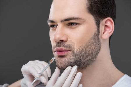 hands in medical gloves making beauty injection for bearded man, isolated on grey
