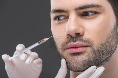 close up of hands in medical gloves making beauty injection for man, isolated on grey