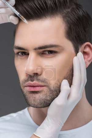hands in medical gloves making beauty injection for handsome man, isolated on grey