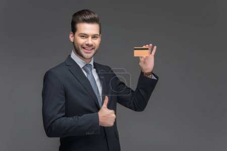 smiling businessman holding golden credit card and showing thumb up, isolated on grey