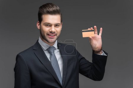 handsome cheerful businessman holding golden credit card, isolated on grey