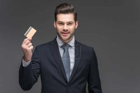 cheerful businessman holding credit card, isolated on grey