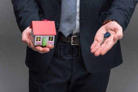Photo pour Recadrée vue d'agent immobilier, tenue de la maison modèle et enfoncée, isolé sur gris - image libre de droit