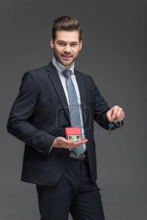 real estate agent holding house model and key, isolated on grey