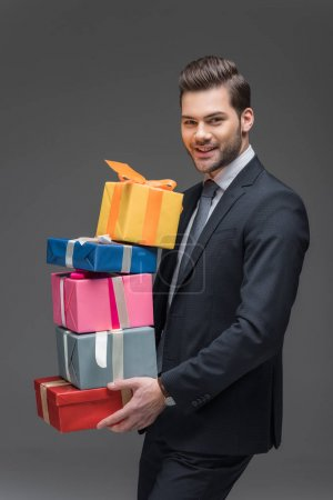 handsome man holding gift boxes, isolated on grey