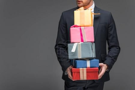 cropped view of man holding gift boxes, isolated on grey
