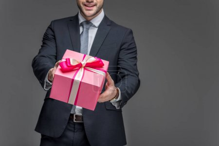 cropped view of man in suit holding gift box, isolated on grey