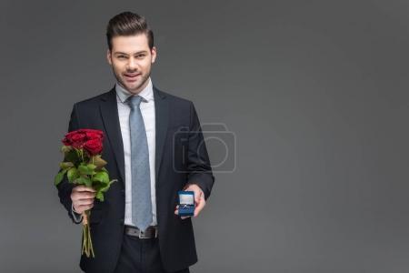 bel homme élégant tenant le bouquet de roses rouges et anneau de proposition, isolé sur fond gris