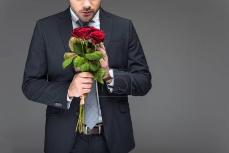cropped view of man holding bouquet of red roses, isolated on grey