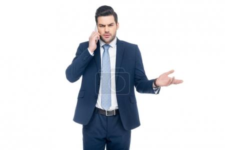 doubtful businessman in suit talking on smartphone, isolated on white