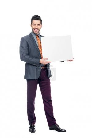 Photo for Smiling businessman in suit holding blank placard, isolated on white - Royalty Free Image