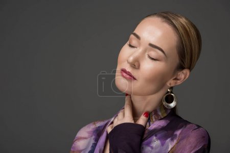 portrait of sensual kazakh woman with closed eyes posing isolated on grey