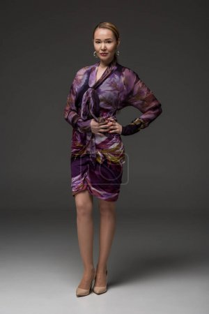 full length view of stylish kazakh woman looking at camera on grey