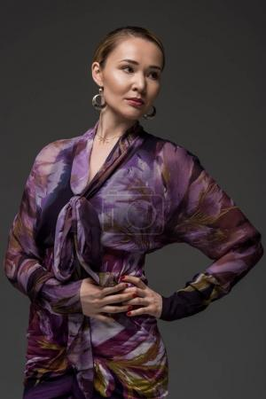 portrait of elegant kazakh woman posing with hands on waist and looking away isolated on grey