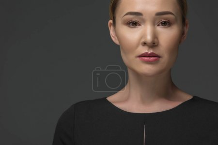 portrait of beautiful kazakh woman looking at camera isolated on grey