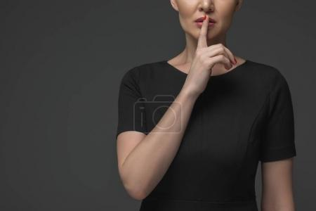 cropped shot of kazakh woman gesturing for silence isolated on grey