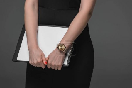 close-up partial view of businesswoman holding clipboard isolated on grey
