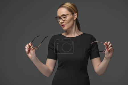 beautiful kazakh woman in black dress choosing eyeglasses isolated on grey