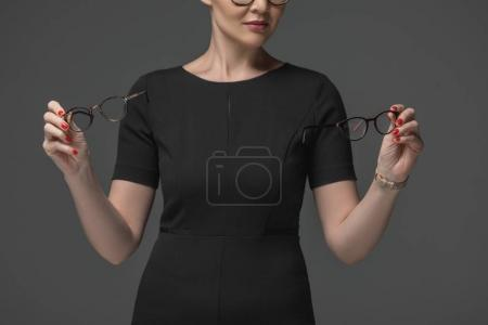 cropped shot of woman in black dress choosing eyeglasses isolated on grey