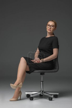 Photo for Beautiful kazakh woman in eyeglasses sitting on chair and looking at camera on grey - Royalty Free Image