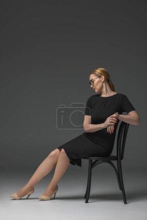 Photo pour Vue sur toute la longueur élégante femme kazakh à lunettes et à la mode robe noire assis sur chaise sur fond gris - image libre de droit