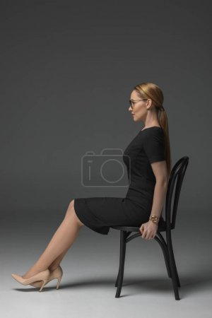 Photo for Side view of beautiful kazakh woman in eyeglasses sitting on chair and looking away on grey - Royalty Free Image